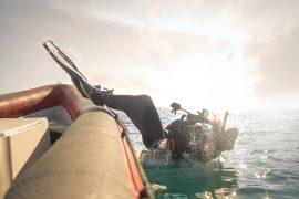 Scuba Taucher springt ins Wasser