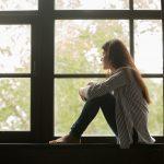 Einsames Mädchen auf der Fensterbank