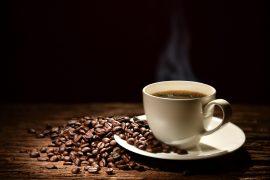 Eine dampfende Tasse Kaffe mit Kaffeebohnen