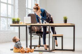 Mutter telefoniert und schaut gleichzeitig nach Baby im Büro