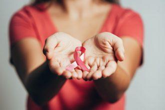 Frau mit pinker Schleife auf Händen