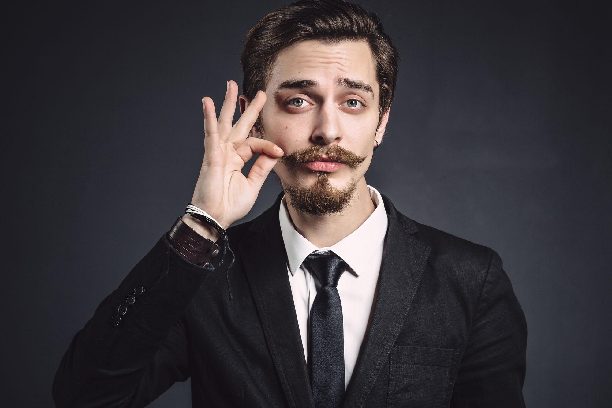 Mann im Anzug der seinen Bart zwirbelt
