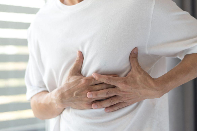 Mann hält sich die schmerzende Brust