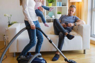 Frau mit Kind auf dem Arm saugt Staub während Mann auf dem Sofa sitzt und Handy nutzt