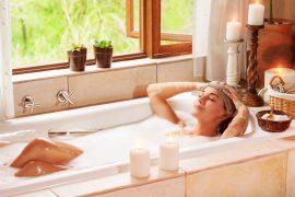 Frau entspannt in Badewanne bei Kerzenschein
