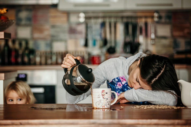 Junge Frau verschüttet vor Müdigkeit Kaffe auf dem Küchentisch.